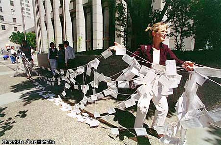About 80 to 100 consumer activists gathered in front of the corporate headquarters of Pacific Gas and Electric--77 Beale St. 5000 postcards from consumers supporting rolling back electricity rates by around 20%percent were strung up for the rally. Liz Hafalia Photo: Liz Hafalia
