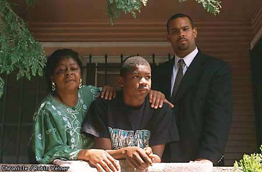 Harold Carter, 13, center, poses with his mom Virginia Ray Cooper, left, and his mentor Ray Bobbitt, a representative of the Father Figure Project, at Carter's Oakland home. Carter has been adopted by the City of Oakland to help him through school after he survived a stabbing several weeks ago by gang members. Robin Weiner/The Chronicle