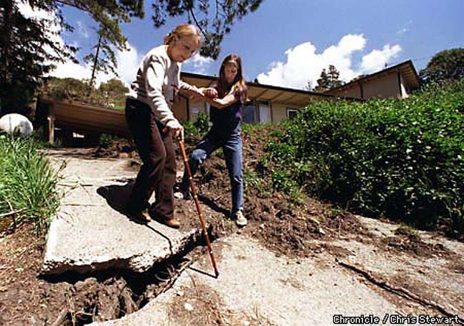 Ellie Wenzel (L) is helped by her daughter Jeanne LePage as they descend the damaged driveway of Wenzel's home on Scenic Drive in La Honda. The Wenzel home has dropped eight feet due to a landslide that has damaged seven homes in the neighborhood. SAN FRANCISCO CHRONICLE PHOTO BY CHRIS STEWART Photo: CHRIS STEWART