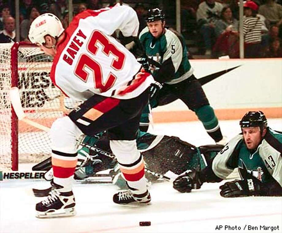 San Jose Sharks' Al Iafrate (43) fights off an attack by Calgary Flames' Aaron Gavey (23) during the first period Saturday, April 18, 1998, at the San Jose Arena in San Jose, Calif. San Jose's Ken Sutton (5) looks on. (AP Photo/Ben Margot) Photo: BEN MARGOT