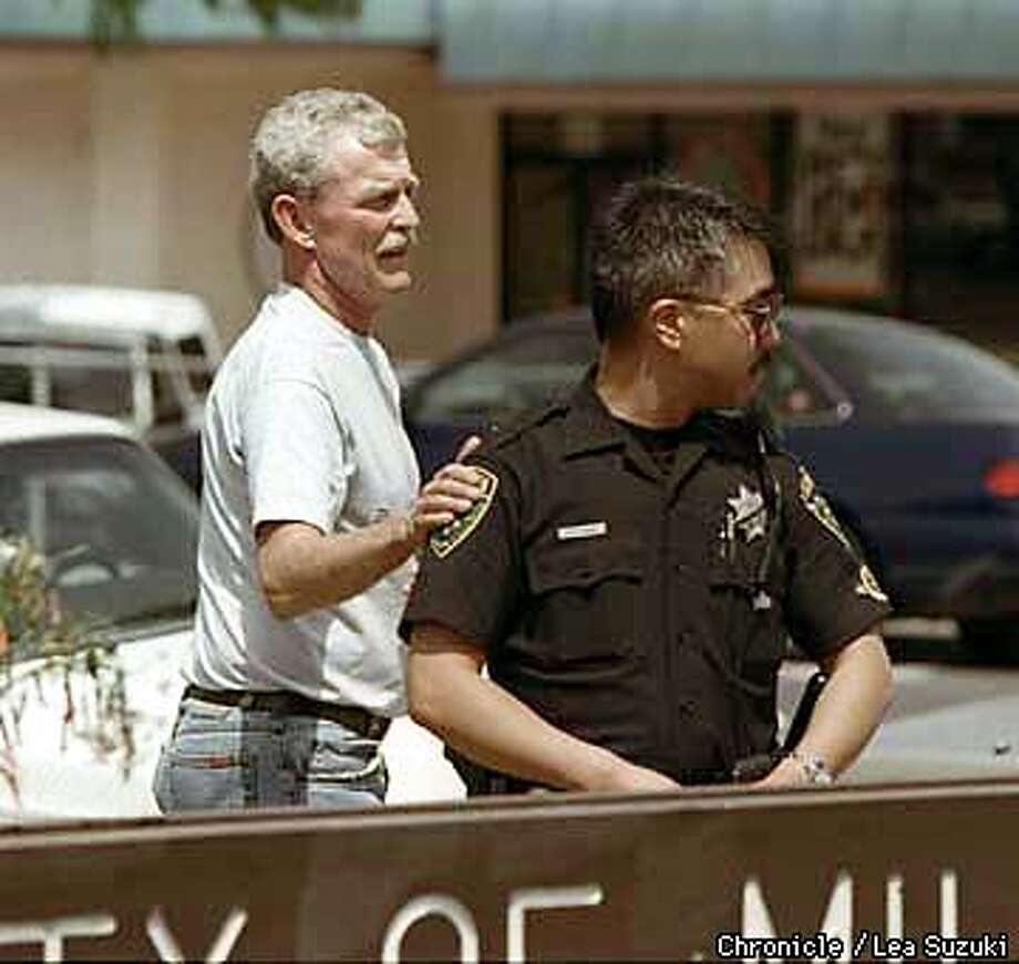 Officer Dan Young, who is also a motorcycle cop like Chetcuti with the Millbrae Police Deparment, gets a consoling pat on the shoulder by Michael Loveseth of Millbrae, as he looks over the Memorial in front of the Millbrae Police station. PHoto By Lea Suzuki Photo: LEA SUZUKI