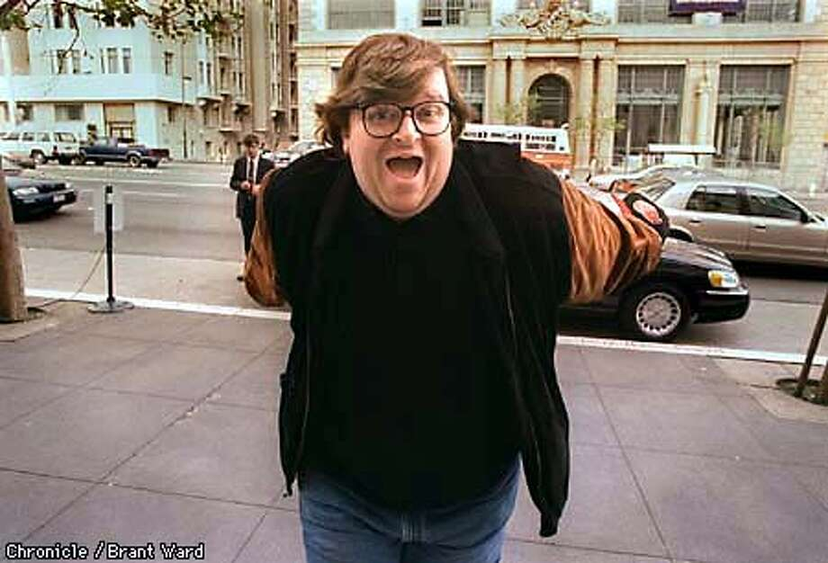 Filmmaker Michael Moore playfully rushed the photographer after he discovered his picture was being taken on Van Ness Avenue. By Brant Ward/Chronicle