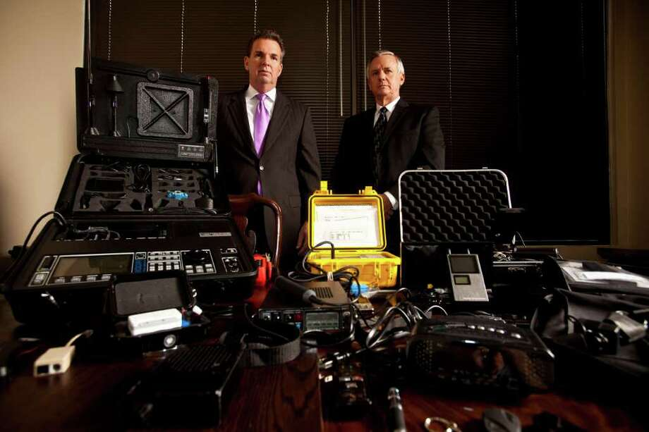 Rob Kimmons and Jim Dunbar of Kimmons Investigative Services, Inc. pose next to their tools of the trade - devices that detect bugs and other gadgets that surreptitiously record audio, video or data., Jan. 20, 2012 in Houston at their office. (Eric Kayne/For the Chronicle) Photo: Eric Kayne / © 2011 Eric Kayne