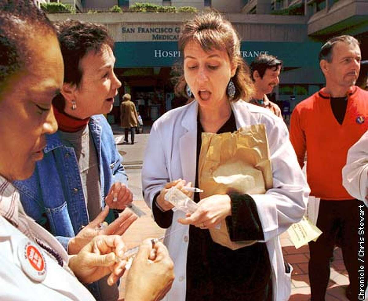 Lisa Ryan, a nurse practitioner at SF General Hospital, is amazed at a demonstration of a safety needle during a rally outside the hospital to protest the lack of safety needles available to health care workers. A hundred people attended the rally to hear speeches by community activists, union leaders and SF Supervisor Tom Ammiano. Explaining the needles effectiveness is Suki Fayette (in blue denim jacket), a registered nurse and clinical coordinator for Retractable Technology, a Texas-based maker of medical safety products. At left, RN E.J. Jellins also looks at the needles. SAN FRANCISCO CHRONICLE PHOTO BY CHRIS STEWART