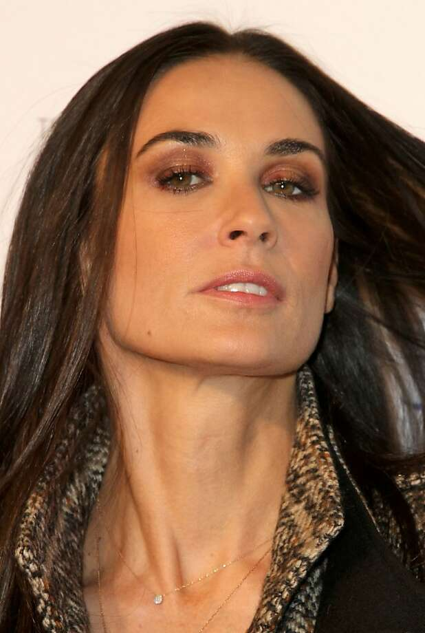 """(FILES)Actress Demi Moore arrives for the Lotus Cars Launch event in this November 12, 2010 file photo in Los Angeles, California.  Actress Demi Moore was convulsing and """"burning up"""" after taking an unidentified drug when emergency services were called earlier this week, according to the 911 call released on January 27, 2012. During the 10-minute call friends tell the 911 operator that the 49-year-old, who split from her younger husband Ashton Kutcher in November after his alleged infidelity, has """"been having some issues lately."""" """"She's convulsing so we're holding her down,"""" said one of three people who take turns to speak to the operator, repeatedly asking him to send an ambulance urgently to her Beverly Hills home.   Moore and 33-year-old Kutcher announced their separation in November, after months of media reports about problems between the couple, who married in 2005. She had earlier been married to actor Bruce Willis for 13 years. AFP PHOTO/VALERIE MACON (Photo credit should read VALERIE MACON/AFP/Getty Images) Photo: Valerie Macon, AFP/Getty Images"""
