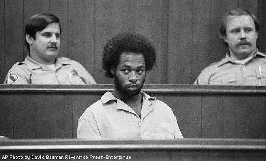 Horace Kelly, the suspect in the Thanksgiving Day murder of an 11-year-old boy, sits in Riverside, Calif., Municipal Court during his arraignment Dec. 5, 1985. Behind Kelly are Riverside Sherrifs Department deputies David Strnad (cq), left, and Al Barker. Kelly, 38, is scheduled to be executed April 14, 1998 for murdering two women and a child in 1984. But his attorney says Kelly is so mentally disturbed he has no idea what is happening to him. AP Photo by David Bauman Riverside Press-Enterprise