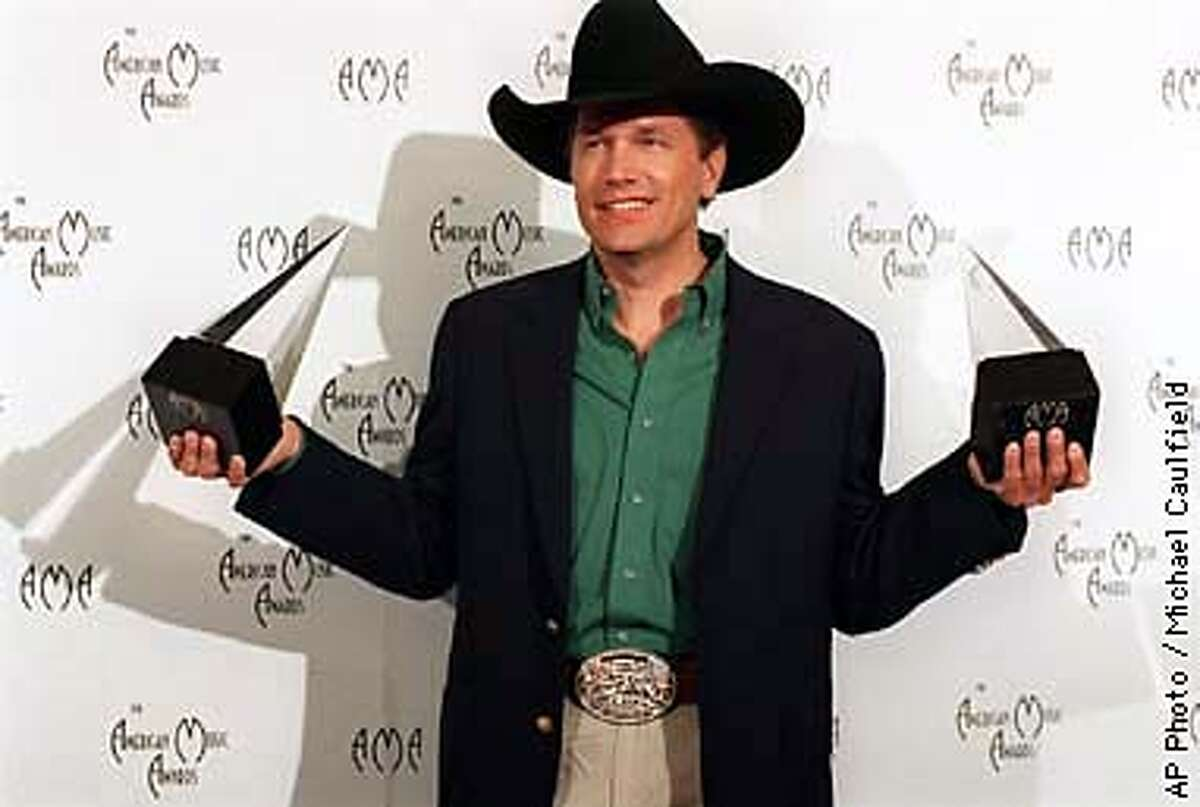 George Strait holds trophies for best country artist and best country album at the 25th annual American Music Awards Monday, Jan. 26, 1998, in Los Angeles. (AP Photo/Michael Caulfield)