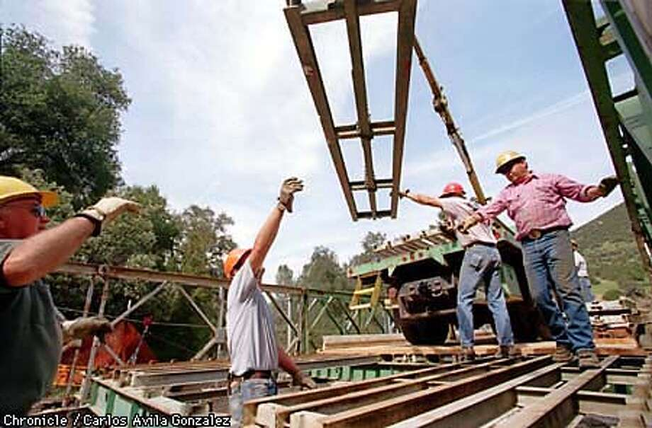 Members of the U.S. Forestry Service move a section of a temporary bridge into place in the Pinnacles National Park where El Ni�o-driven storms washed out the bridge that connected two sections of the park. The bridge will be in place for about a year and a half, and will be replaced when the creek it crosses is drier. (CHRONICLE PHOTO BY CARLOS AVILA GONZALEZ) Photo: CARLOS AVILA GONZALEZ