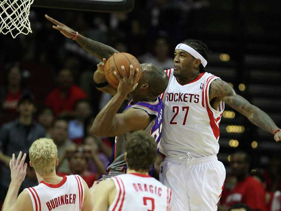 Jordan Hill, right, makes it tough on Michael Redd on a night the Rockets take a defensive stand. Photo: Karen Warren / © 2012  Houston Chronicle