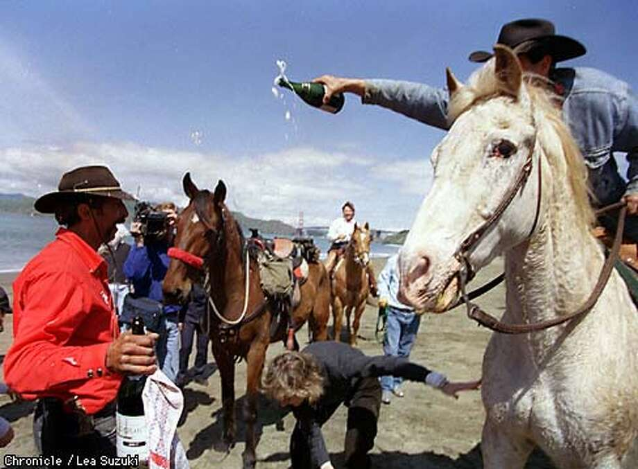 Ray Piecuch is doused with champagne by Keith Simon of Woodside, riding his horse Howard, after finishing his cross country trek ending at Baker Beach on Sunday afternoon. Bo, Piecuch's horse who made the cross country trek with Piecuch, is in background with red nose band. Photo By Lea Suzuki Photo: LEA SUZUKI