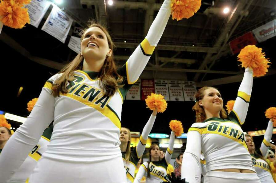Siena cheerleaders Kathleen Hess, 21, left, and Amanda Willey, 21, right, show support for their tea