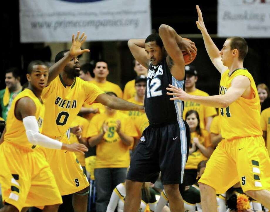 St. Peter's Darius Conley (42), center, looks for help as Siena's Evan Hymes (5), left, Brandon Walters (0) and Owen Wignot (31), right, put on the pressure during their basketball game on Friday, Feb. 3, 2012, at Times Union Center in Albany, N.Y. (Cindy Schultz / Times Union) Photo: Cindy Schultz /  00015373K