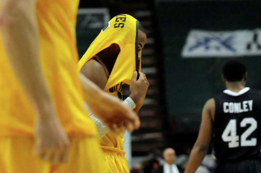 Siena's Evan Hymes (5), center, pulls his uniform over his head when they lose 63-58 in their basket