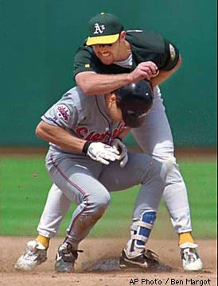 Cleveland Indians' Travis Fryman, front, collides with Oakland Athletics' Scott Spiezio during a second-inning double play Wednesday, April 8, 1998, at the Oakland (Calif.) Coliseum. Cleveland's Jeff Manto was out at first base. AP Photo by Ben Margot