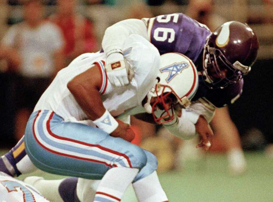 Minnesota Vikings linebacker Chris Doleman (56) brings down Houston Oilers quarterback Warren Moon for a safety during preseason NFL football action in Minneapolis in August 1990.  Photo: Jim Mone