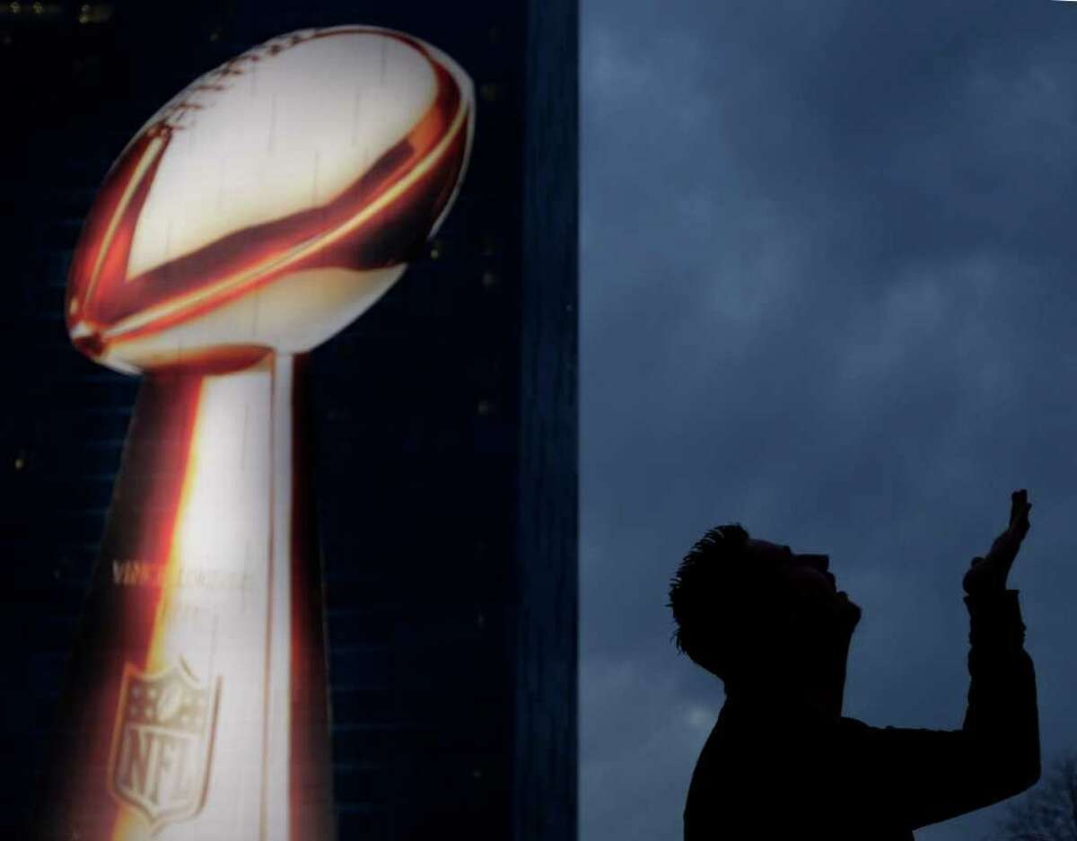 Kyle Weaver, of Elwood, Ind., poses for a photo in front of a hotel displaying a likeness of the Vince Lombardi Trophy Friday, Feb. 3, 2012 in Indianapolis. The New England Patriots are scheduled to face the New York Giants in NFL football's Super Bowl XLVI on Feb. 5. (AP Photo/Charlie Riedel)