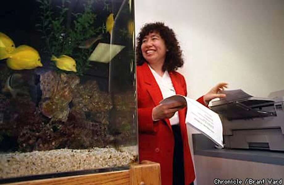 Marilyn Leong loves her fax machine almost as much as her fish now that she saves gobs of money faxing around the nation. She is an executive with California Pacific Association. By Brant Ward/Chronicle
