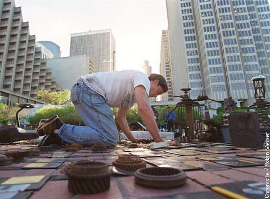 "Joe Mangrum, artist of Berkeley, adds to his installation art or ephemeral sculpture called ""Trans-mission 98"" at Justin Herman Plaza. Photo by Robin Weiner Photo: ROBIN WEINER"