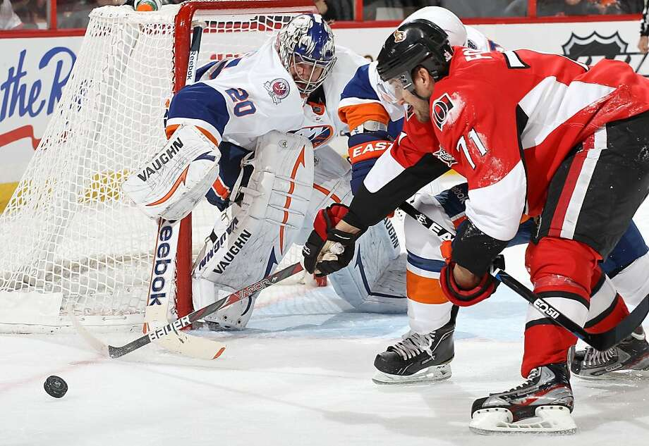 Nick Foligno #71 of the Ottawa Senators reaches for the loose puck as Evgeni Nabokov #20 of the New York Islanders defends the net during an NHL game at Scotiabank Place on February 3, 2012 in Ottawa, Ontario, Canada. Photo: Jana Chytilova/Freestyle Photo, Getty Images