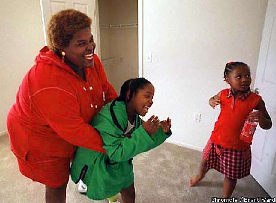 Angela Stevenson grabbed her daughter Reanna and got the giggles as the two celebrated their new public housing apartment. They loved the large closets, in background. Angela's niece Jasmine is at right. By Brant Ward/Chronicle