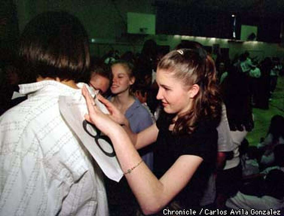 Eighth grader Rose Pendleton, 13, pins her partner's number on his back, during the Ballroom Dance competition at Kennedy Middle School. Her partner, seventh grader Sasha Savonic, 13, was dancing in the eighth grade because Rose was older. (CHRONICLE PHOTO BY CARLOS AVILA GONZALEZ) Photo: CARLOS AVILA GONZALEZ