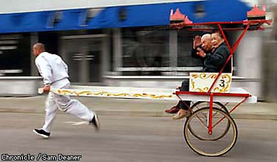 Scuttling down Main Street pulling a rickshaw David De La Rosa takes Tim and June Oyongn, grand marshalls of the Isleton Chinese New Year celebration, on a trial run Thursday. (Chronicle Photo by Sam Deaner) Photo: SAM DEANER