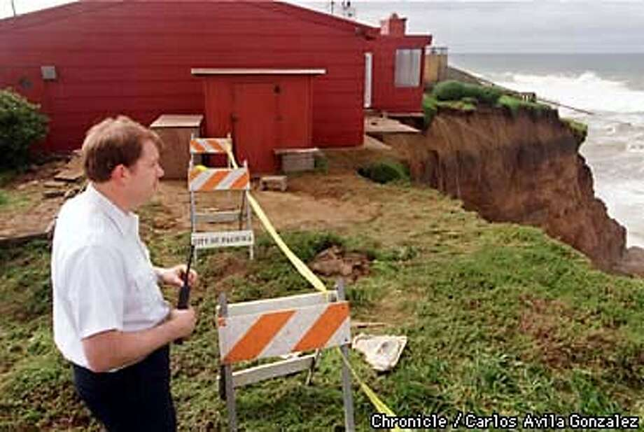 Pacifica City Fire Marshal Steven Brandvold examines the diminishing cliffside behind eight red-tagged homes on Esplanade Drive in Pacifica at high tide on Wednesday morning. City officials decided to cut off the back half of the house in the background to prevent the entire home from falling into the ocean. (CHRONICLE PHOTO BY CARLOS AVILA GONZALEZ) Photo: CARLOS AVILA GONZALEZ