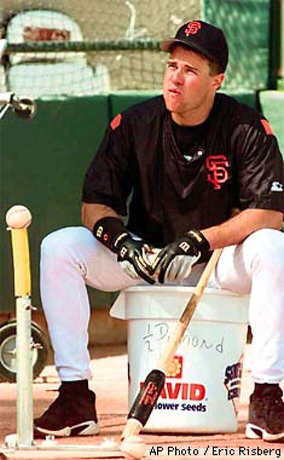 San Francisco Giants first basemand J.T. Snow sits on a seed bucket and places balls on a tee for teammate Jeff Kent prior to their spring training game against the San Diego Padres in Scottsdale, Ariz., Wednesday, March 4, 1998.(AP Photo/Eric Risberg) Photo: ERIC RISBERG