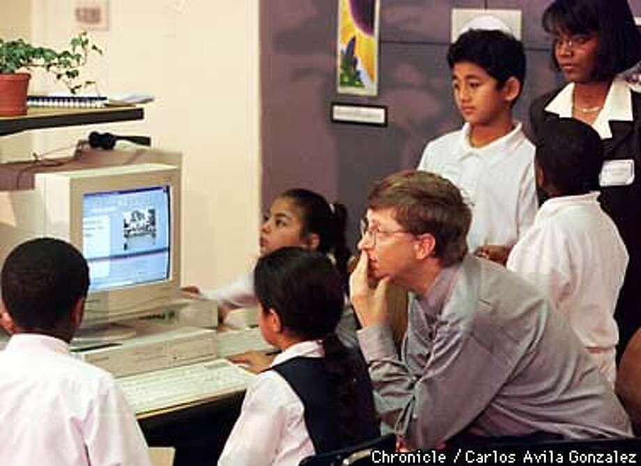 Microsoft chief Bill Gates, looks over computer work by students in Michelle Williams's third grade classroom where Gates visited to see technology in education. (CHRONICLE PHOTO BY CARLOS AVILA GONZALEZ) Photo: CARLOS AVILA GONZALEZ