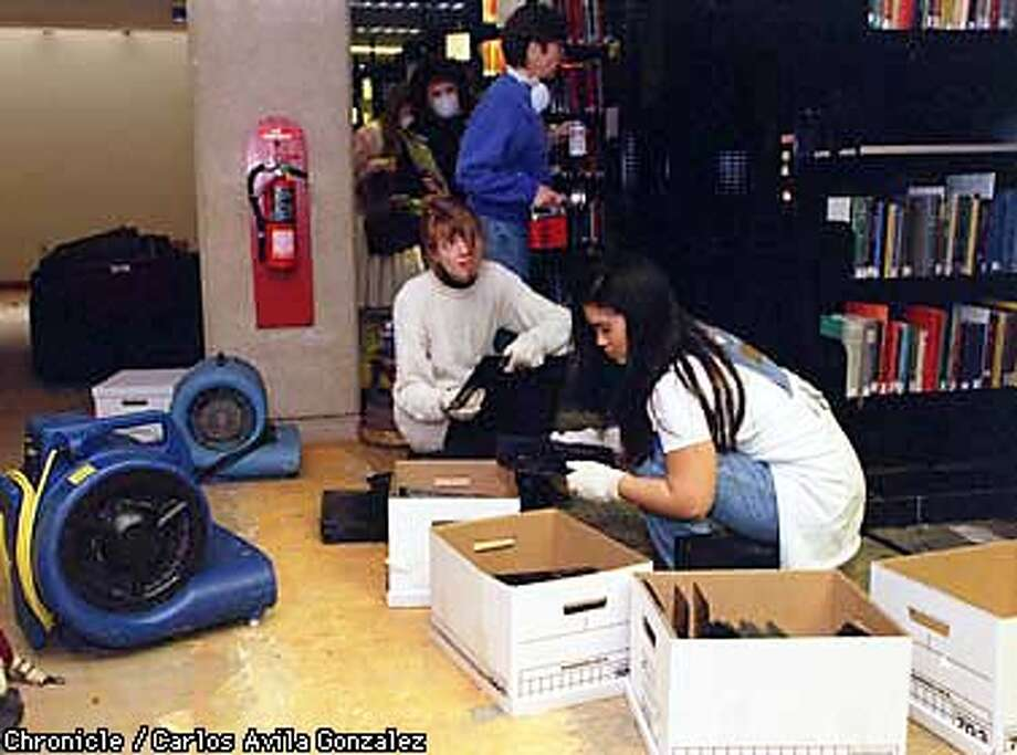 WET BOOKS/C/04FEB98/MN/CG --- Rose Bonsal left, and Jean Shen, of Falconer Biology at Stanford University, are part of a force of library staff and volunteers at Stanford University who picked apart the lower level of Green Library after flood water damaged thousands of books. The books were removed on Tuesday, but those working were cleaning up shelves and removing carpet, and trying to dry out the facilities. (CHRONICLE PHOTO BY CARLOS AVILA GONZALEZ) Photo: CARLOS AVILA GONZALEZ