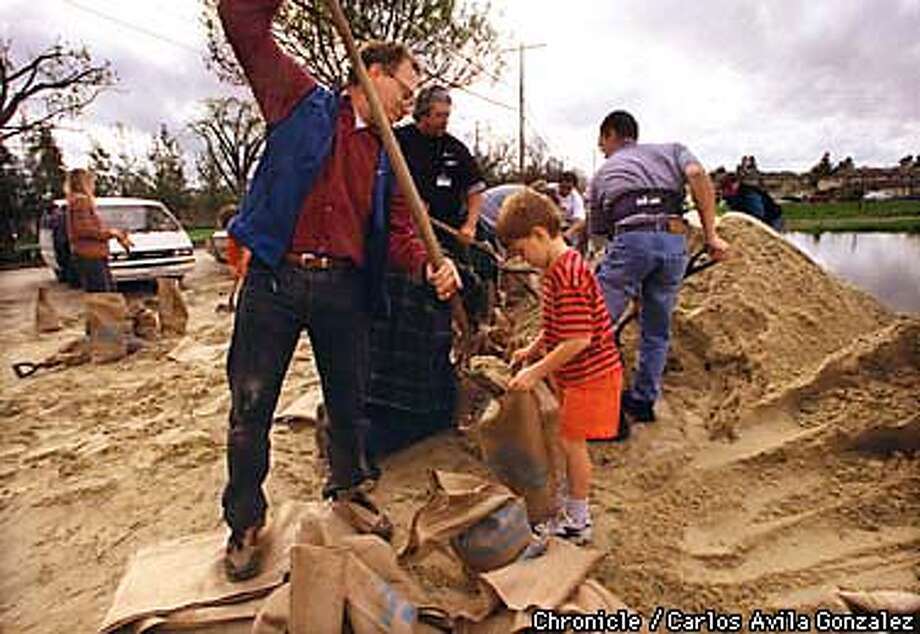 With storm clouds approaching, Dan Stober and his son Andrew, 6, fill sandbags at Greer Park to protect their Palo Alto home. The sand and bags were provided by the county agencies. SAN FRANCISCO CHRONICLE PHOTO BY CARLOS AVILA GONZALEZ Photo: CARLOS AVILA GONZALEZ
