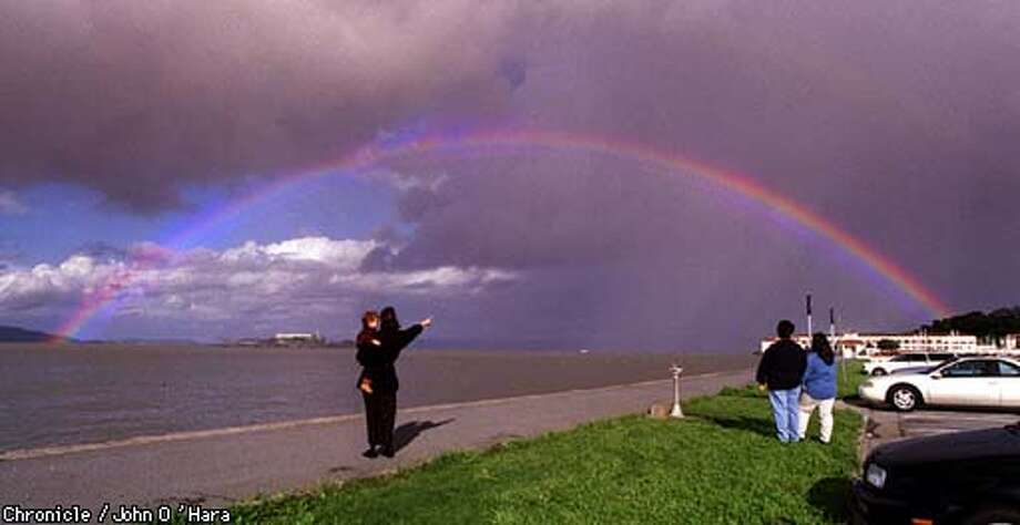 """Changing weather, witnessed by a national audience, """" Laurie Andreozzi and her son Peter (2) from Charlotte North Carolina, and Anna Cruz (middle to right) from SF and her friend Anna Longoria from TEXAS enjoyed the rainbow from Marina Green.  Photo by............John O'Hara"""
