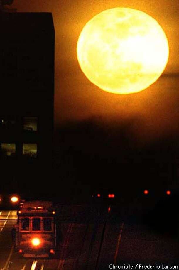MOON WEATHER3/12FEB98/MN/FRL: The San Francisco Bay Area took the night off from raining as the clouds parted (2/11) giving way for the full moon to shine over a cable car making its way down Nob Hill. Chronicle photo by Frederic Larson