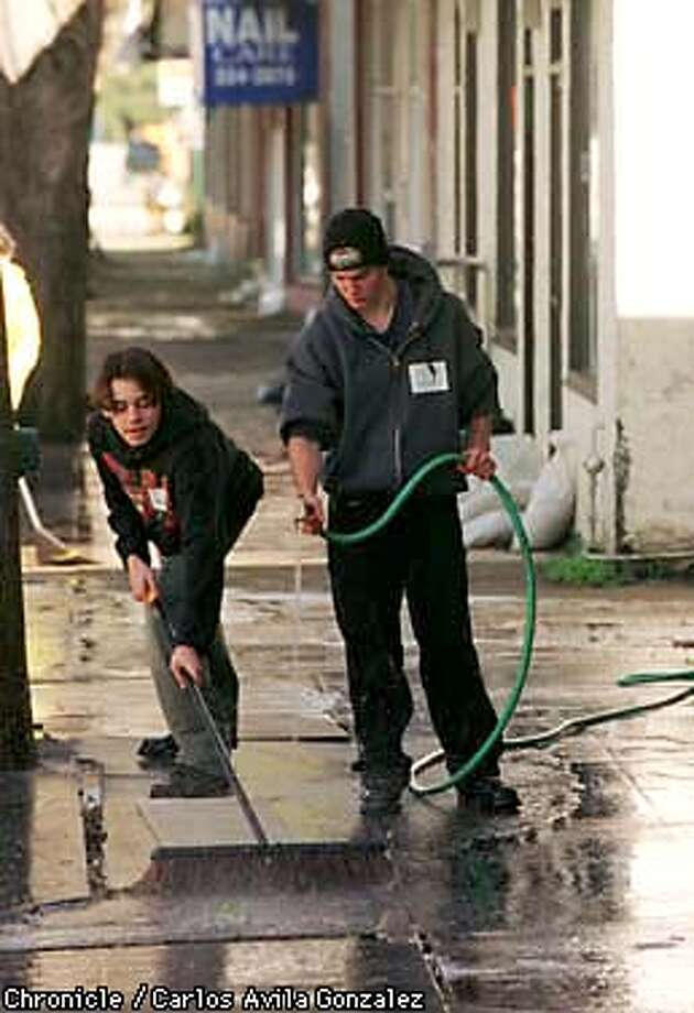Brent Schimik, 15, left, and Anthony Atkins, 15, right, of Carlmont High School, hose down mud soaked rugs from businesses on University Avenue in East Palo Alto where 530 students from the high school volunteered to aid cleanup efforts in the wake of last week's flooding in the area. (CHRONICLE PHOTO BY CARLOS AVILA GONZALEZ) Photo: CARLOS AVILA GONZALEZ