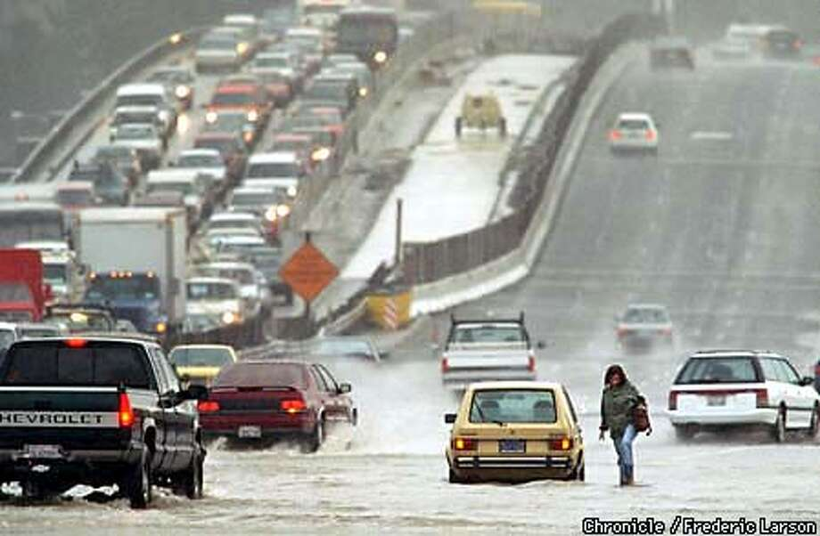 FLOODS LUCKY/C/06FEB98/MN/FRL: A motorist gives up her car going north bound when she stalls out at Lucky Drive exit in Marin. Chronicle photo by Frederic Larson.