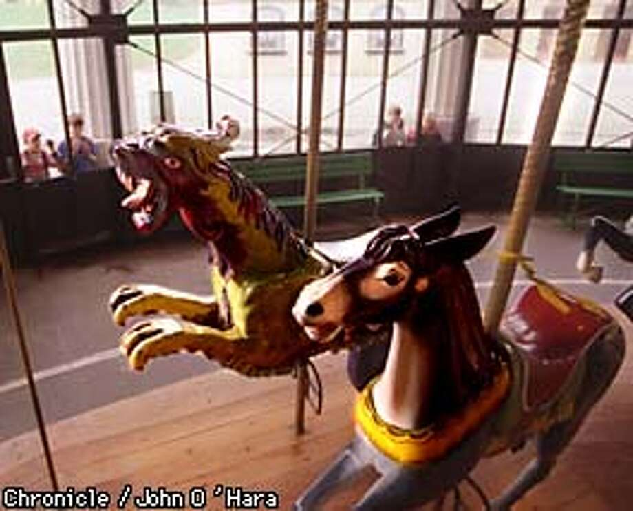"""Golden Gate Park, Playground. """"The Carousel"""". damaged bearings and crankshafts have shut down the Carousel. A Tigercat and Mule at rest while young people looking through the windows of the closed Carousel.  Pphoto by........John O""""Hara"""