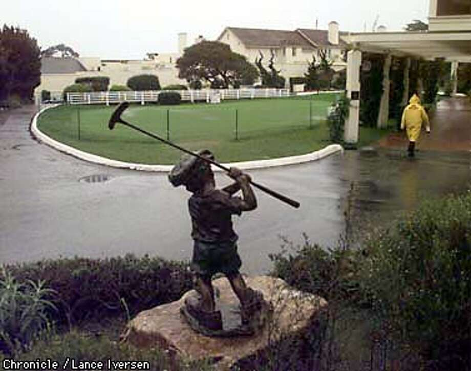 """The normally packed putting green in front of the Pebble Beach Lodge was deserted this morning as word spread of the further postponement of the tournament. In the foreground is a sculpture by artist Walt Horton titled """"Just Like Dad"""".  Photo by Lance Iversen Photo: LANCE IVERSEN"""