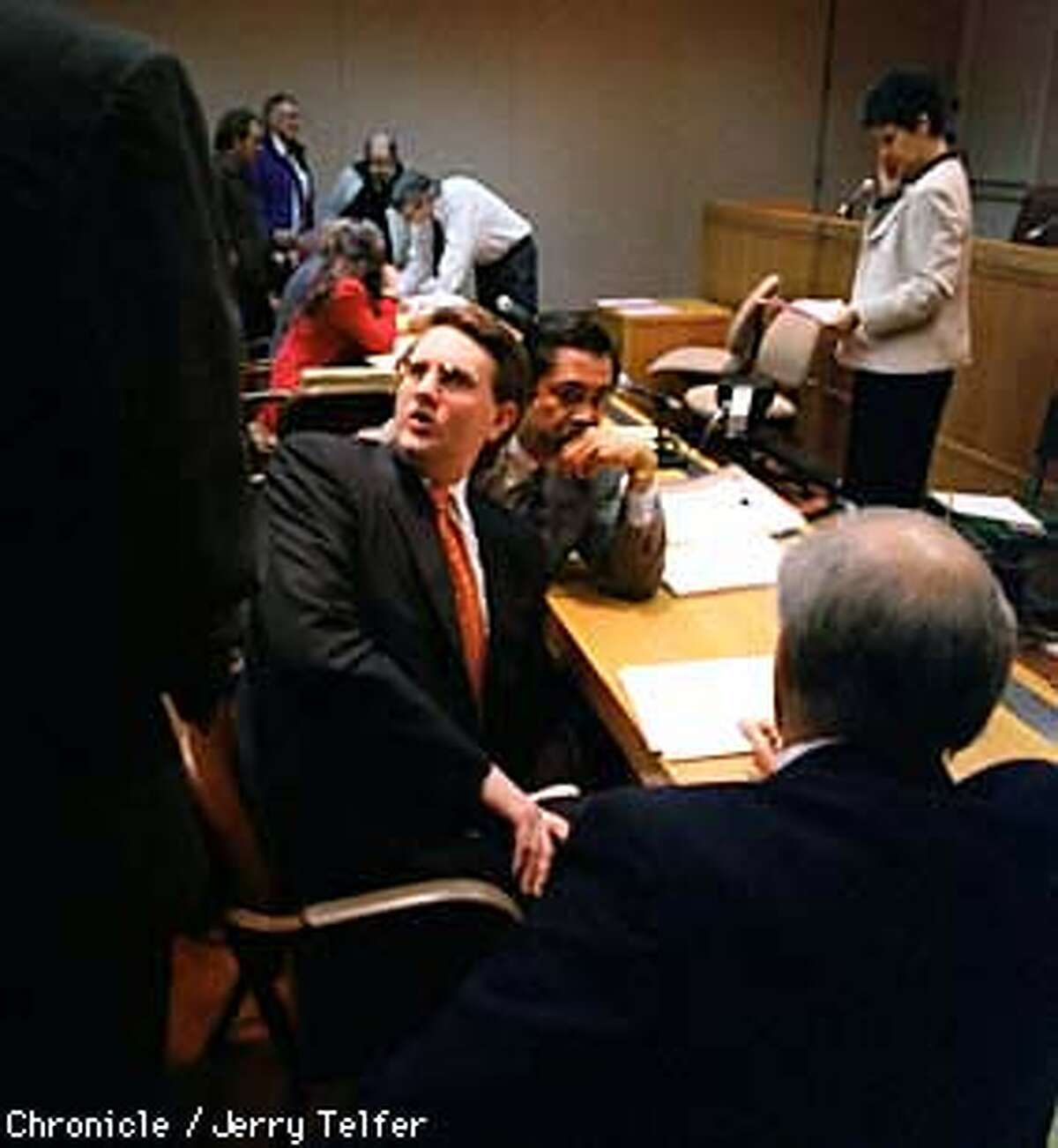 PUC 1/C/13FEB98/BU/JLT Christopher Mee (center, in glasses), head of Boston Finney, confers with associates and lawyers during a brief recess in a California Public Utilities Commission hearing into alleged fraud by his firm. 505 Van Ness Avenue PHOTO BY JERRY TELFER