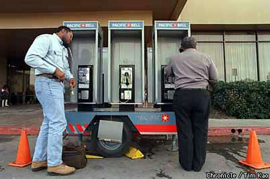 =PACBELL set up a telephone bank outside East Palo Alto Community Center to compensate for a break in telephone line in EPA and PA area. On the phones are (l-r) Vincent May and Eleazar R. Rojas. PHOTO BY TIM KAO/THE CHRONICLE Photo: TIM KAO