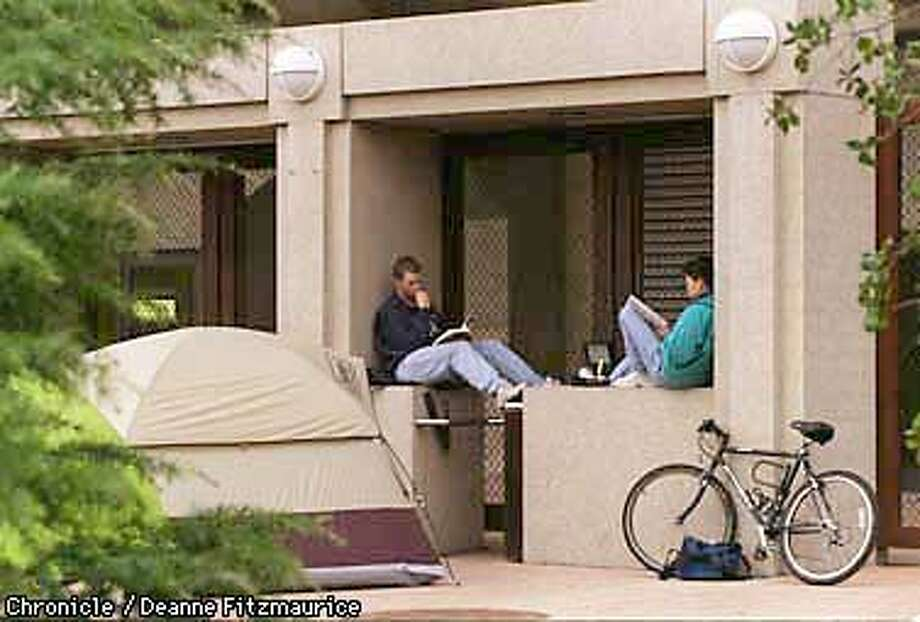 (l to r) Daniel Francis and Chang Kim, both Sophomores at Stanford are camping out at the North entrance to Maples Pavilion in anticipation of Thursday night's basketball game against Arizona. They are doing their homework sitting on top of the turnstiles, and sleeping in a tent so they can get the best seats. CHRONICLE PHOTO BY DEANNE FITZMAURICE Photo: DEANNE FITZMAURICE