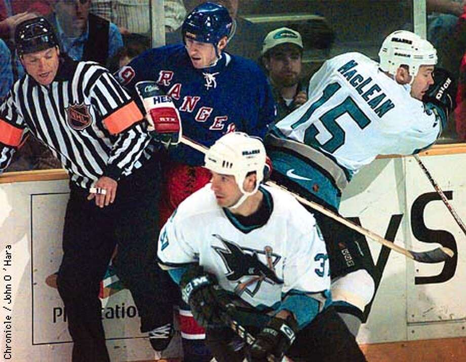 New York Rangers V/S Sharks.  Referee Dan Marouelli Rangers Wayne Gretzky and Sharks John MacLean all collide together.  Stephane Matteau is in foreground.