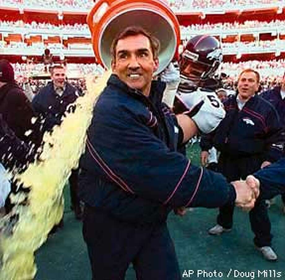 Denver Broncos linebacker Bill Romanowski douses coach Mike Shanahan after beating the Pittsburgh Steelers 24-21 to win the Sunday, Jan. 11, 1998, at Three Rivers Stadium in Pittsburgh. (AP Photo/Doug Mills) Photo: DOUG MILLS
