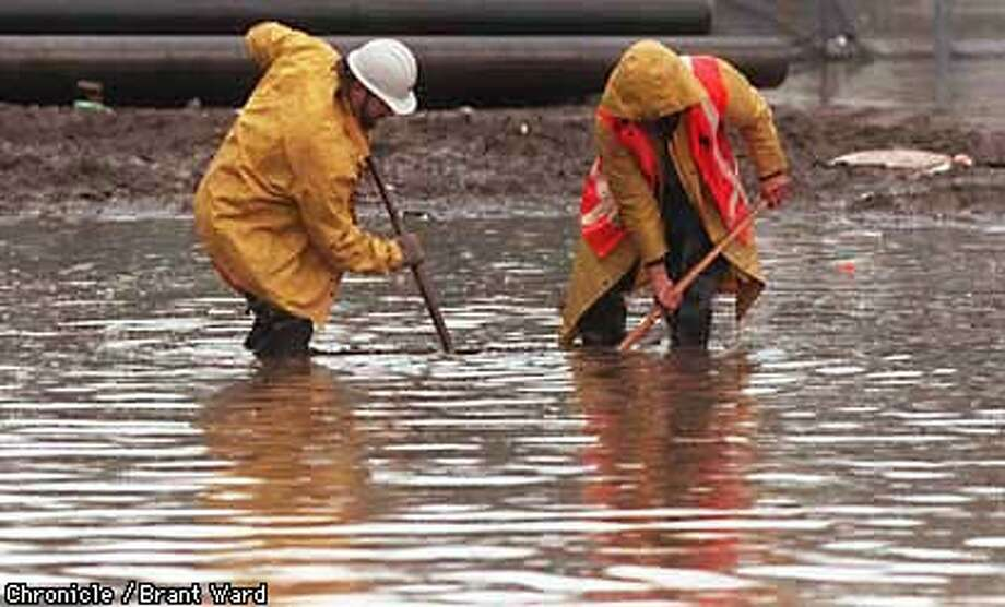 CLOGGED DRAINS/12JAN98/CD/WARD--CALTRANS workers used shovels to clear a drain on Alemany Blvd near Bayshore which shut down the street Monday. By Brant Ward/Chronicle