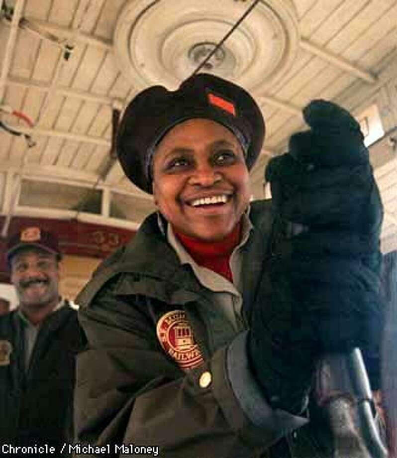 Fannie Mae Barnes keeps two firm hands on the grip as she guides the cablecar down California Street. Behind her is her supervisor/trainer Leonard Turner. Barnes is training to be the first female grip-person to work for Muni. Tomorrow is her official first non - training day on the job.  Photo by Michael Maloney Photo: MICHAEL MALONEY