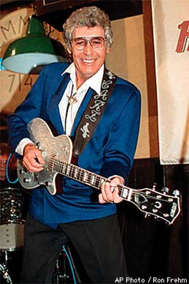 FILE -- Rockabilly legend Carl Perkins performs on stage at New York's Hard Rock Cafe in this Jan. 21, 1992 file photo. Perkins, the rock �n� roll pioneer whose song �Blue Suede Shoes� and lightning-quick guitar-playing influenced Elvis Presley, the Beatles and a slew of other performers, died Monday, Jan. 19, 1998. He was 65. (AP Photo/ Ron Frehm) Photo: RON FREHM