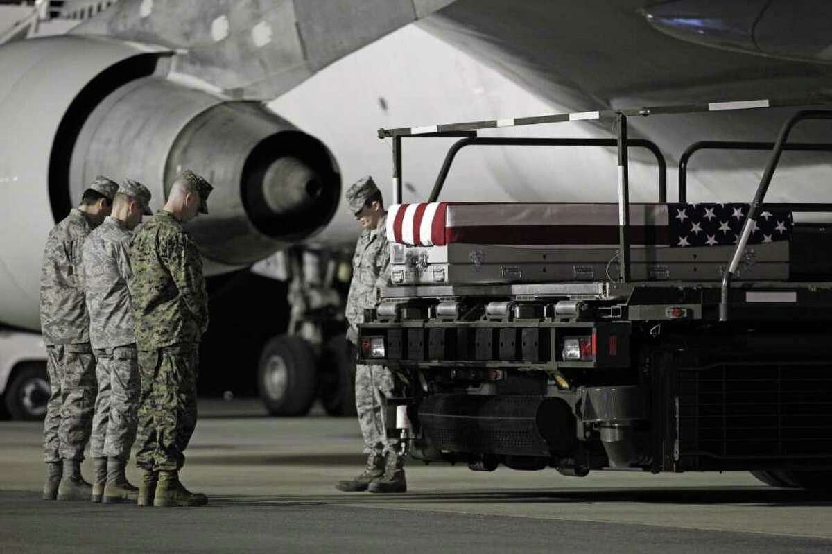 Chaplain Maj. Marty Fields, left, direct a prayer over the transfer case containing the remains of Marine Sgt. William C. Stacey of Redding, Calif., upon arrival at Dover Air Force Base, Del. on Thursday, Feb. 2, 2012. The Department of Defense announced the death of Stacey who was supporting Operation Enduring Freedom in Afghanistan.