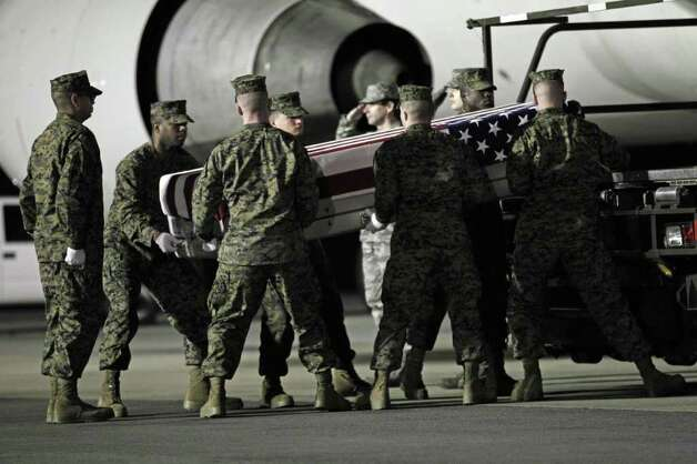 A Marine carry team carries the transfer case containing the remains of Marine Sgt. William C. Stacey of Seattle upon arrival at Dover Air Force Base, Del. on Thursday. Photo: AP