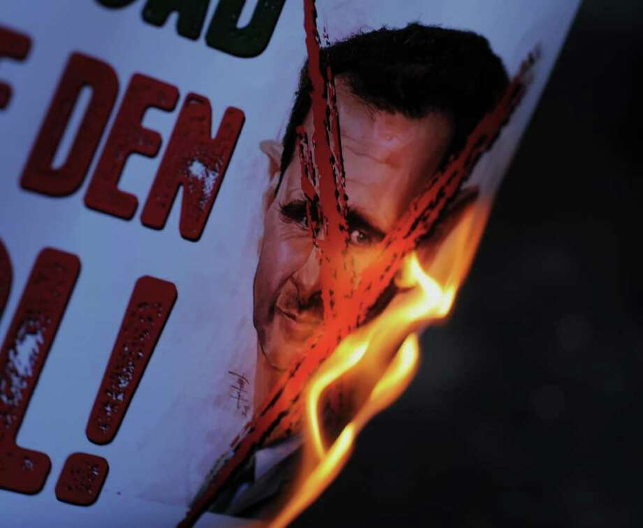 "Protesters set on fire a placard in Turkish that reads "" Assasin Assad, get out of Syria"" as dozens of Syrians living in Turkey and human right activists stage a protest outside the Syrian consulate to condemn the latest killings in Syria, in Istanbul, Turkey, Saturday. (AP Photo) Photo: Anonymous, ASSOCIATED PRESS / AP2012"