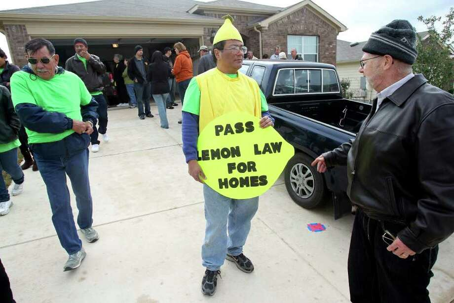 "Charlie Sanchez (center) holds a protest sign as residents of the Fairhaven subdivision hold an ""open house"" to show structural problems in their homes on Saturday, Feb. 4, 2012. Photo: Tom Reel, San Antonio Express-News / San Antonio Express-News"