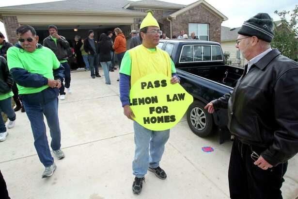 "Charlie Sanchez (center) holds a protest sign as residents of the Fairhaven subdivision hold an ""open house"" to show structural problems in their homes on Saturday, Feb. 4, 2012."
